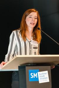 Dr.Theresa Hamilton, Mitarbeiterin des Grund-Bildungs-Zentrum, stellt das Alpha-Siegel vor.